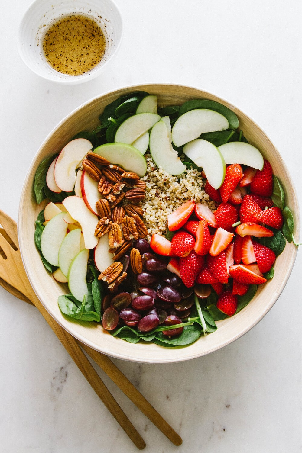 top down view of a large serving bowl filled with the prepped spinach salad ingredients before mixing.