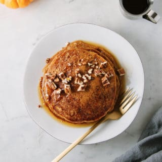 vegan pumpkin pancakes with chopped walnuts and maple syrup
