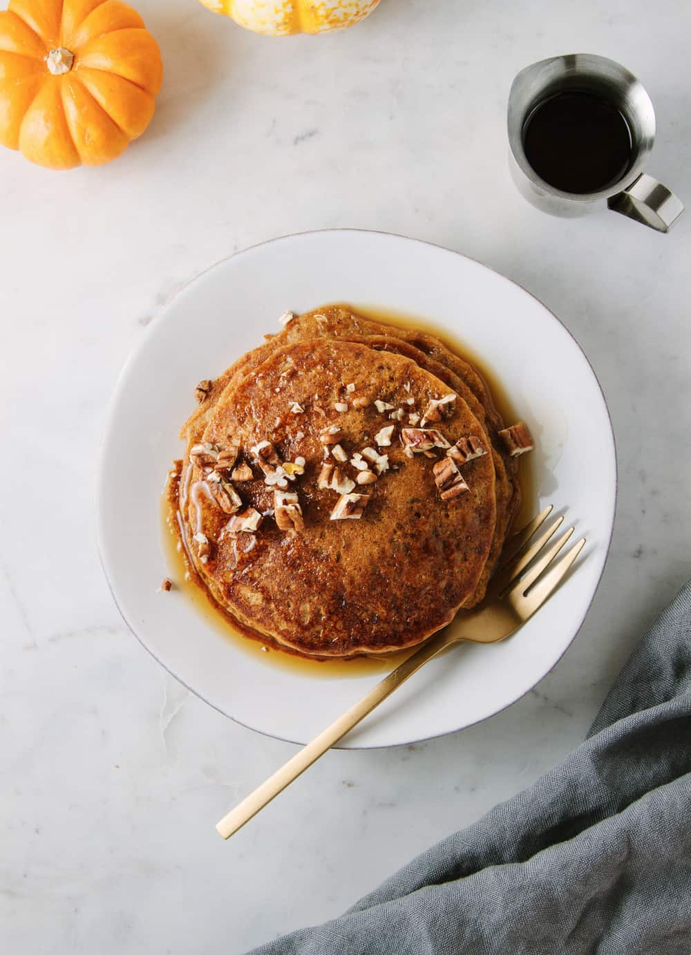 vegan pumpkin pancakes with chopped pecans and maple syrup