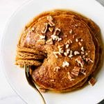 vegan pumpkin spice pancakes with chopped walnuts and maple syrup ready to eat