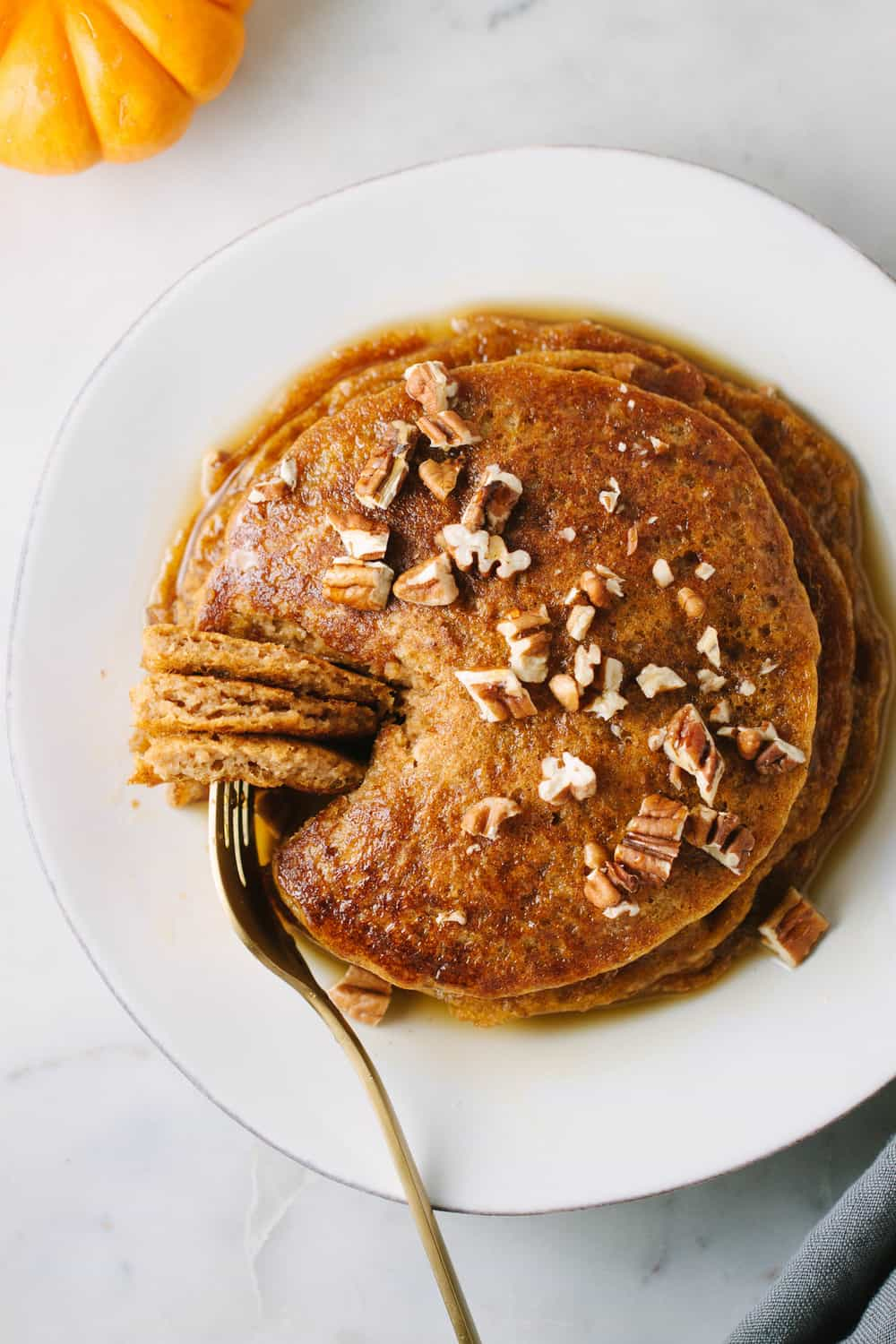 vegan pumpkin spice pancakes with chopped pecans and maple syrup ready to eat