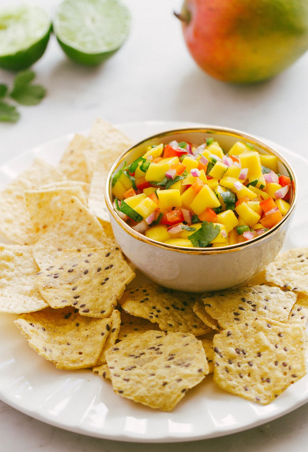 bowl of mango salsa with chips on a white plate
