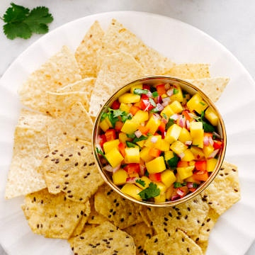 top view of mango salsa in a bowl with chips on a white plate