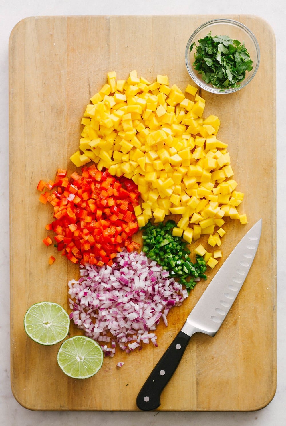 mango salsa ingredients on a cutting board, mangos, red pepper, onion, jalapeno, cilantro and lime