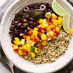 top down view of cuban black beans, mango salsa and quinoa in a bowl