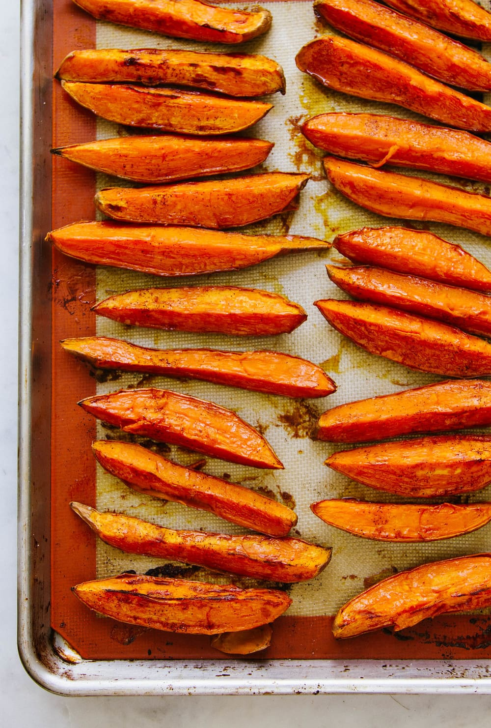 top down view of freshly baked sweet potatos on a rimmed baking sheet just pulled from the oven
