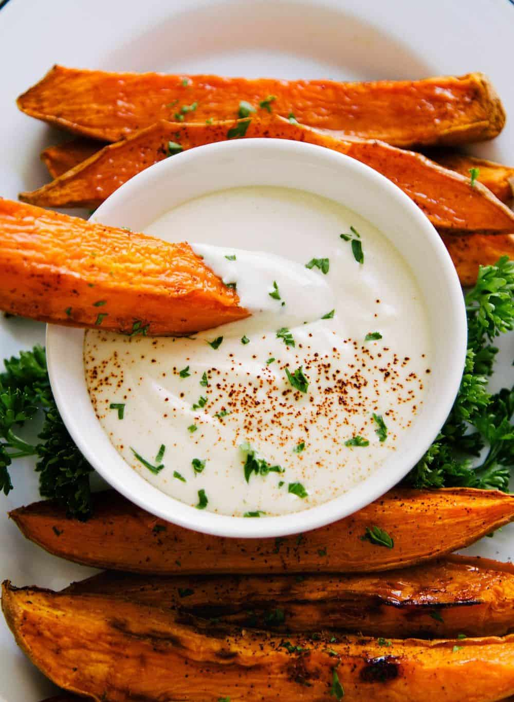 baked sweet potato wedges with vegan garlic aioli sauce for dipping