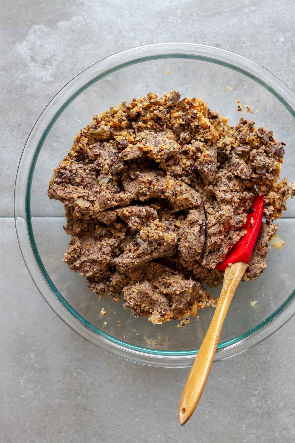 processed black bean burger ingredients in a large glass bowl and mashed together.