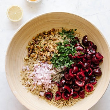a bowl with quinoa, sliced cherries, mint, pistachios and red onion