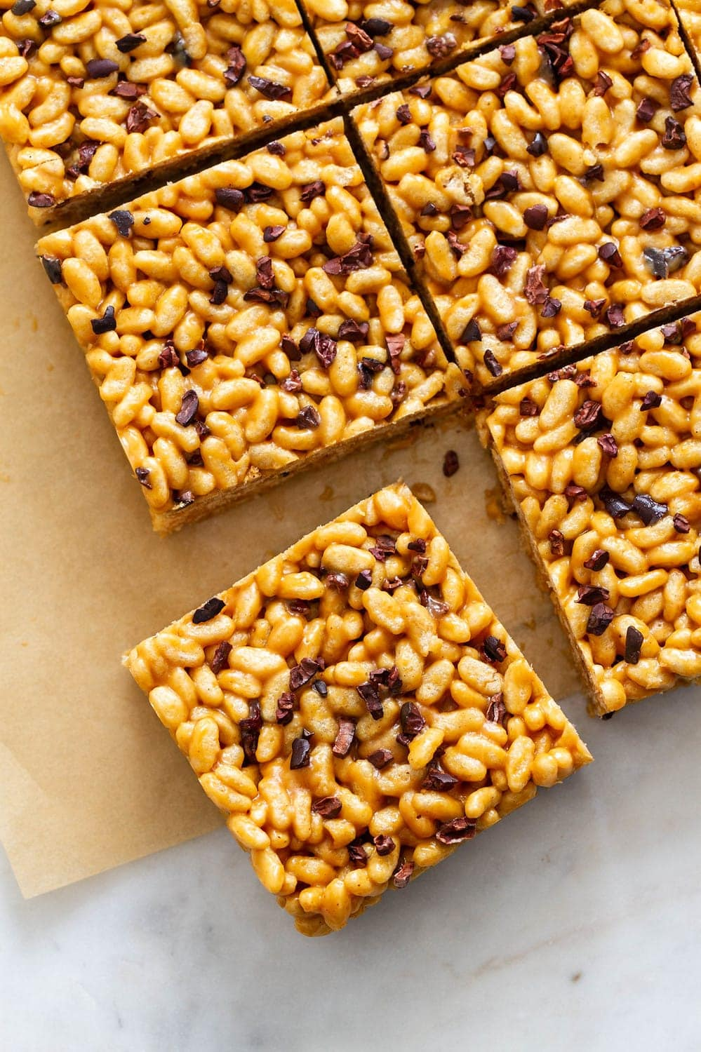 top down view of peanut butter cacao nibs rice crispy treats on parchment paper sliced into squares