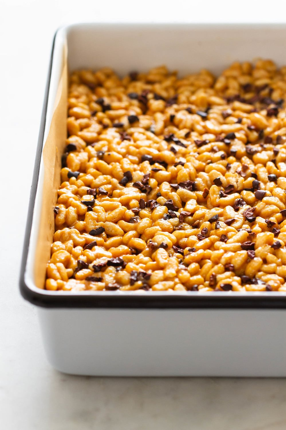 side angle view of peanut butter cacao nibs rice crispy treats pressed into a square white baking pan with black rim