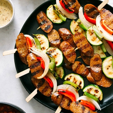 top down view of grilled veggie and kielbasa skewers on a black plate