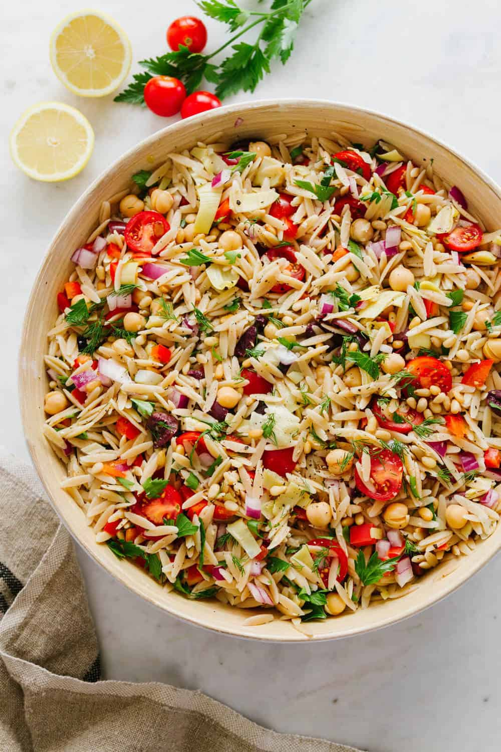 greek orzo salad in large wooden serving bowl