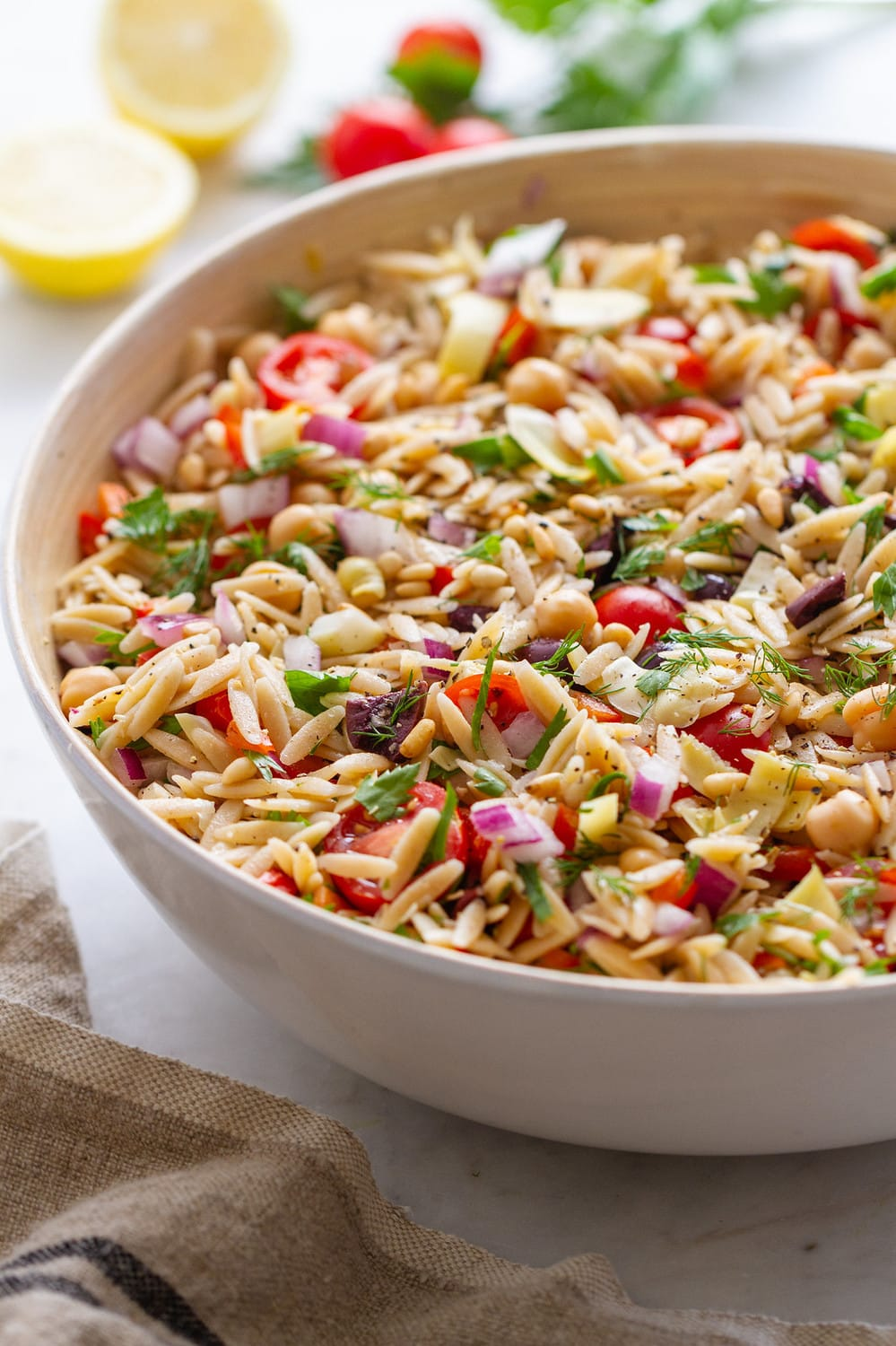 side view of a big bowl of mediterranean orzo salad