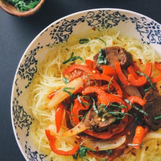spaghetti squash with peppers, onion and sausage in a white bowl