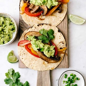 vegan portobello fajitas on corn tortilla with avocado guacamole