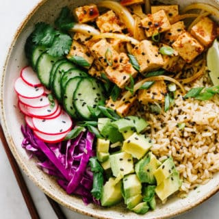 spicy tofu poke bowl with sprouted brown rice, avocado, cucumber, radish, red cabbage, green onions, lime wedges and black sesame seeds