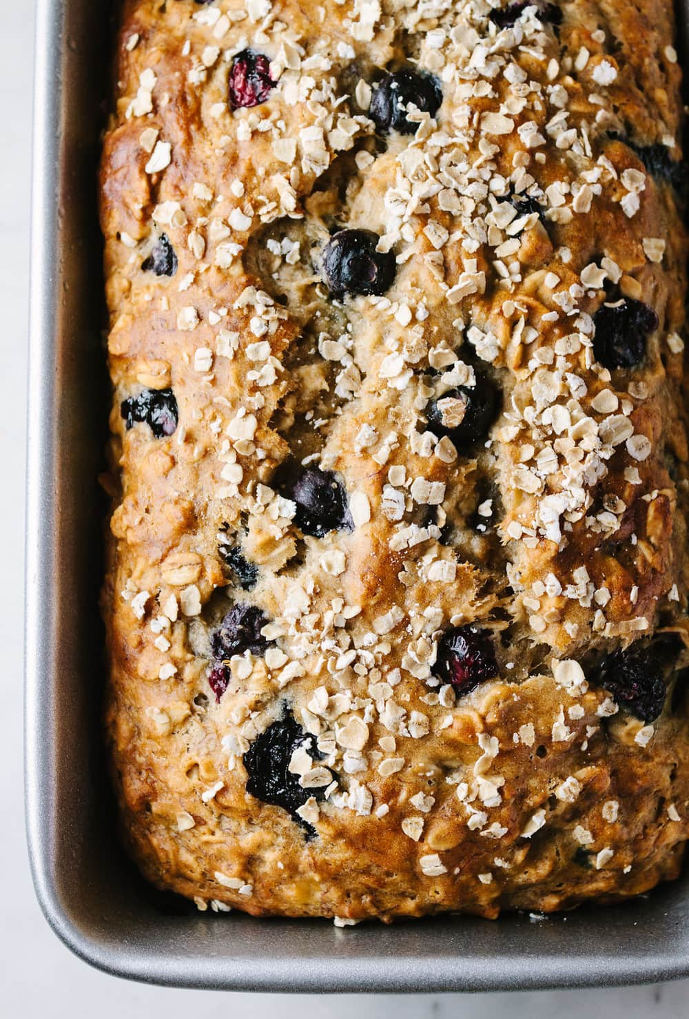 top down view of freshly baked vegan blueberry banana oat bread in loaf pan