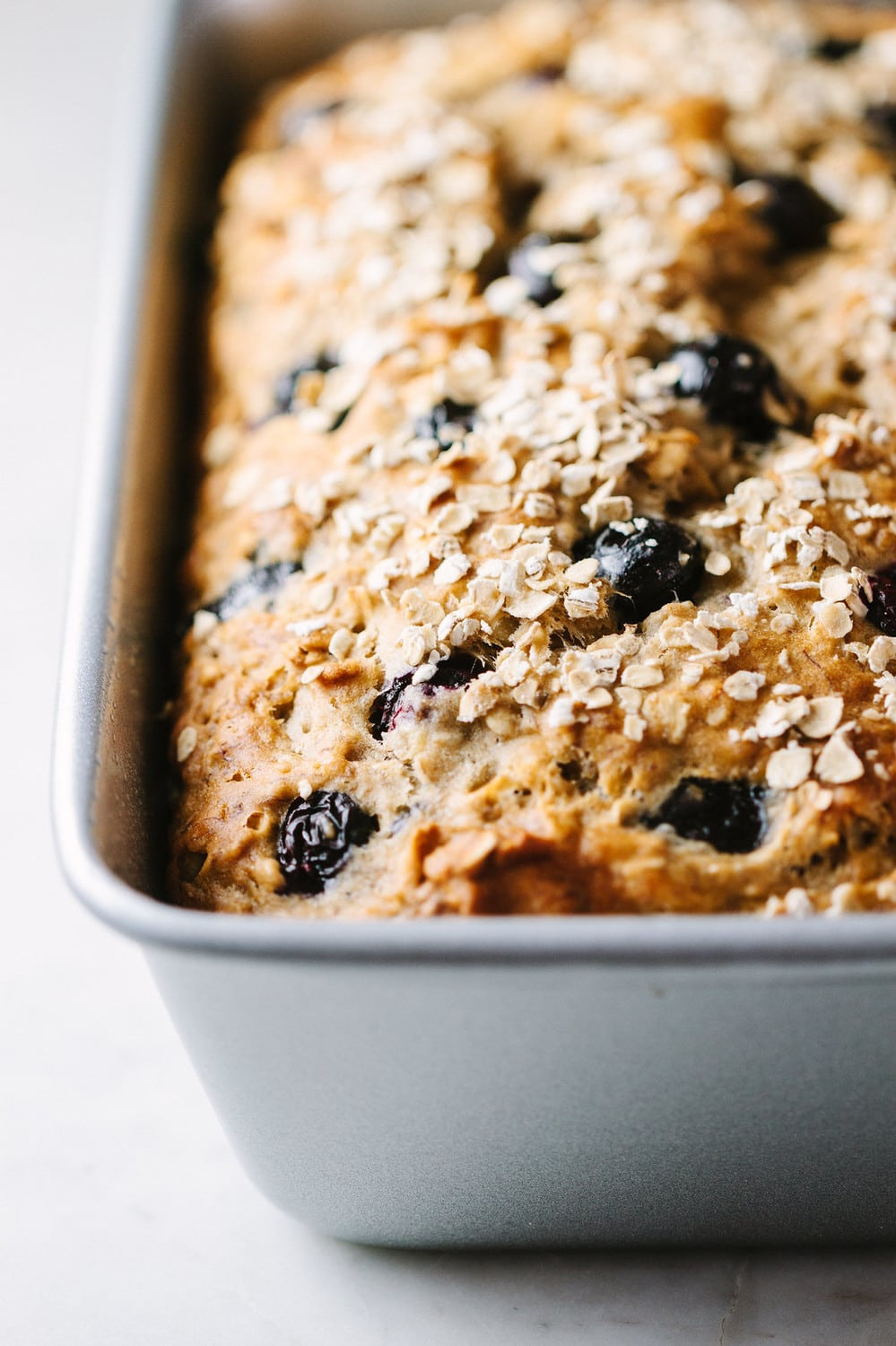 vegan blueberry banana oat bread in a loaf pan just baked