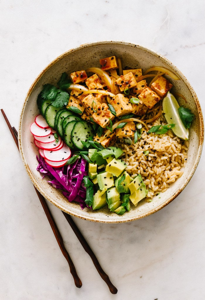 spicy vegan hawaiian tofu poke bowl with sprouted brown rice, avocado, cucumber, radish, red cabbage, green onions, lime wedges and black sesame seeds