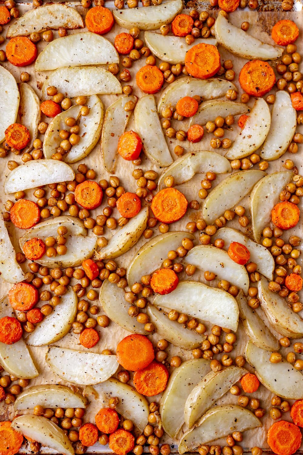 top down view of roasted chickpeas, potatoes and carrots on a rimmed baking sheet.