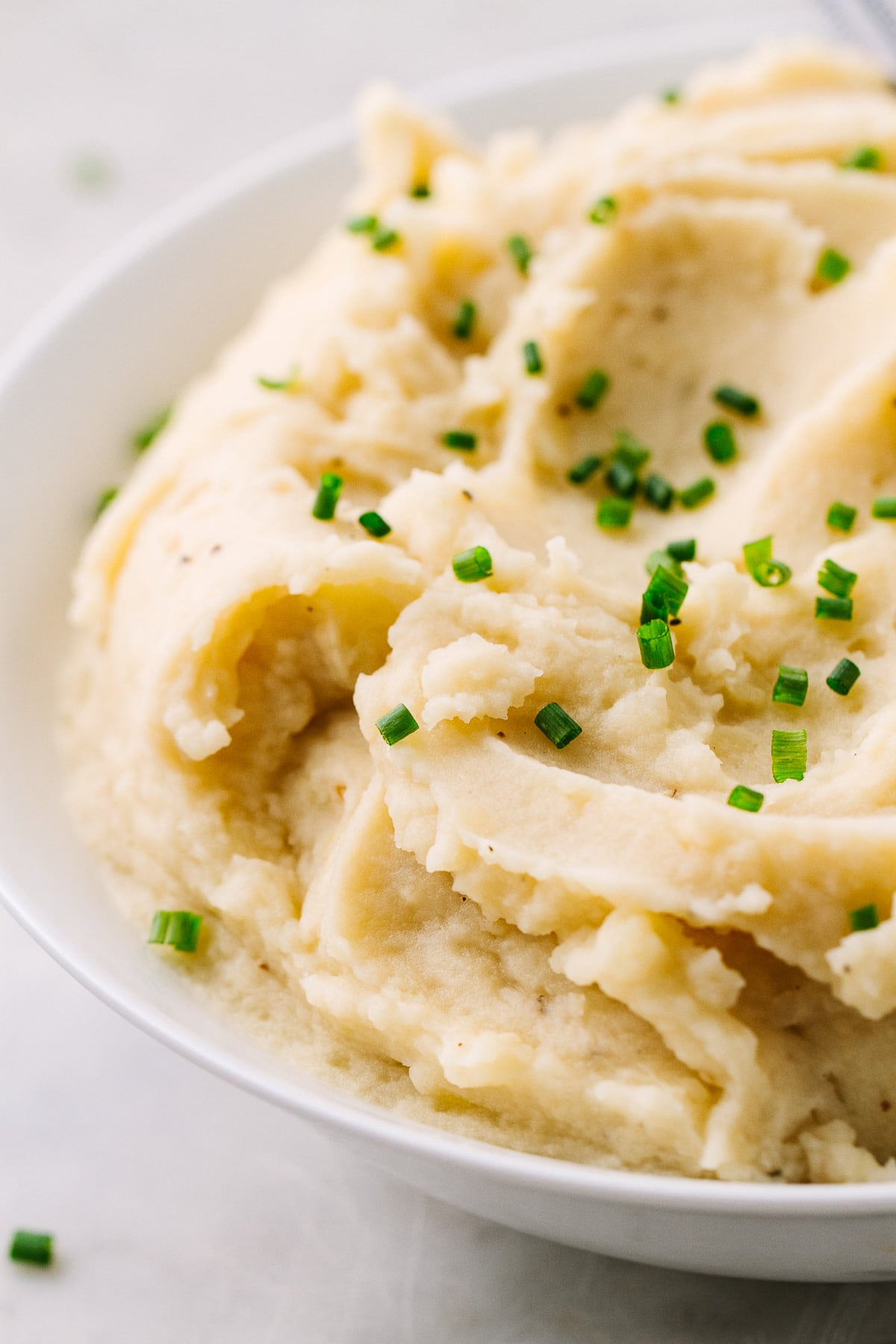 side angle view of instant pot vegan mashed potatoes in a bowl with chopped chives on top.