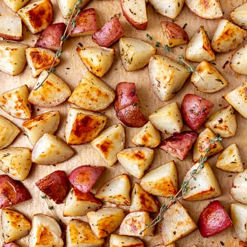 top down view of a baking sheet lined with parchment paper and freshly oven roasted red potatoes with thyme sprigs
