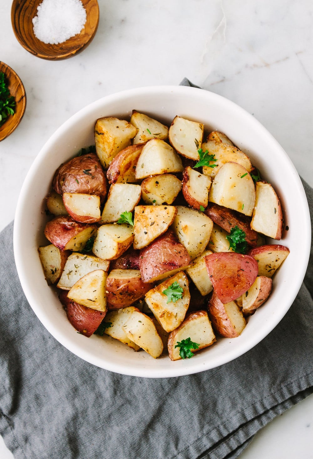 top down view of oven roasted red potatoes in a white serving bowl on top of a grey linen napkin