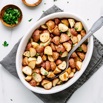 top down view of a white serving bowl with oven roasted red potatoes.