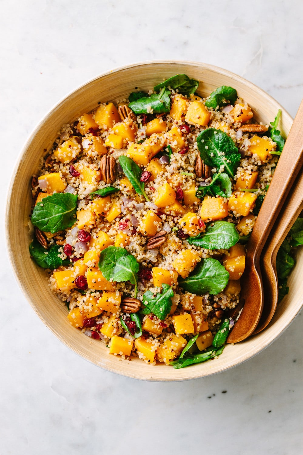top down view of a serving bowl filled with butternut squash quinoa salad with wooden serving utensils