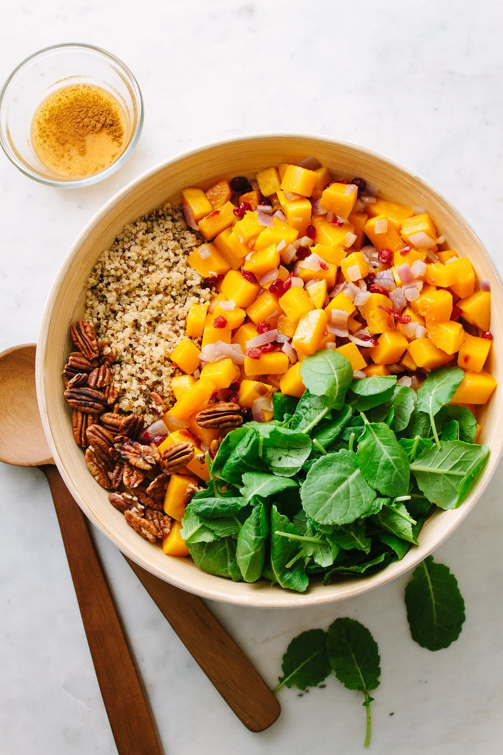top down view of all the ingredients added to a bowl and ready to be mixed: ingredients include roasted butternut squash, quinoa, toasted pecans, baby spinach and cinnamon orange dressing