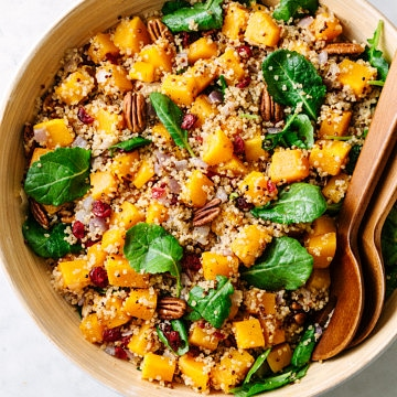 top down view of roasted butternut squash quinoa salad with pecans in a large serving bowl with wooden utensils.