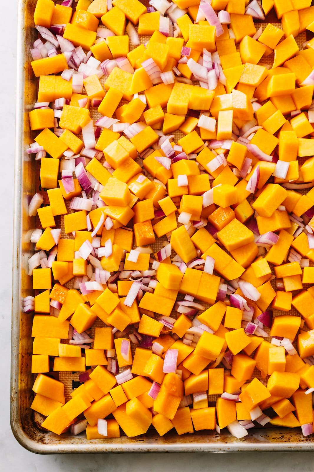 top down view of butternut squash and red onion on a rimmed baking sheet ready for the oven.