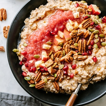 top down view of cinnamon oatmeal with applesauce, pecans, apples, pomegranetes in a black bowl