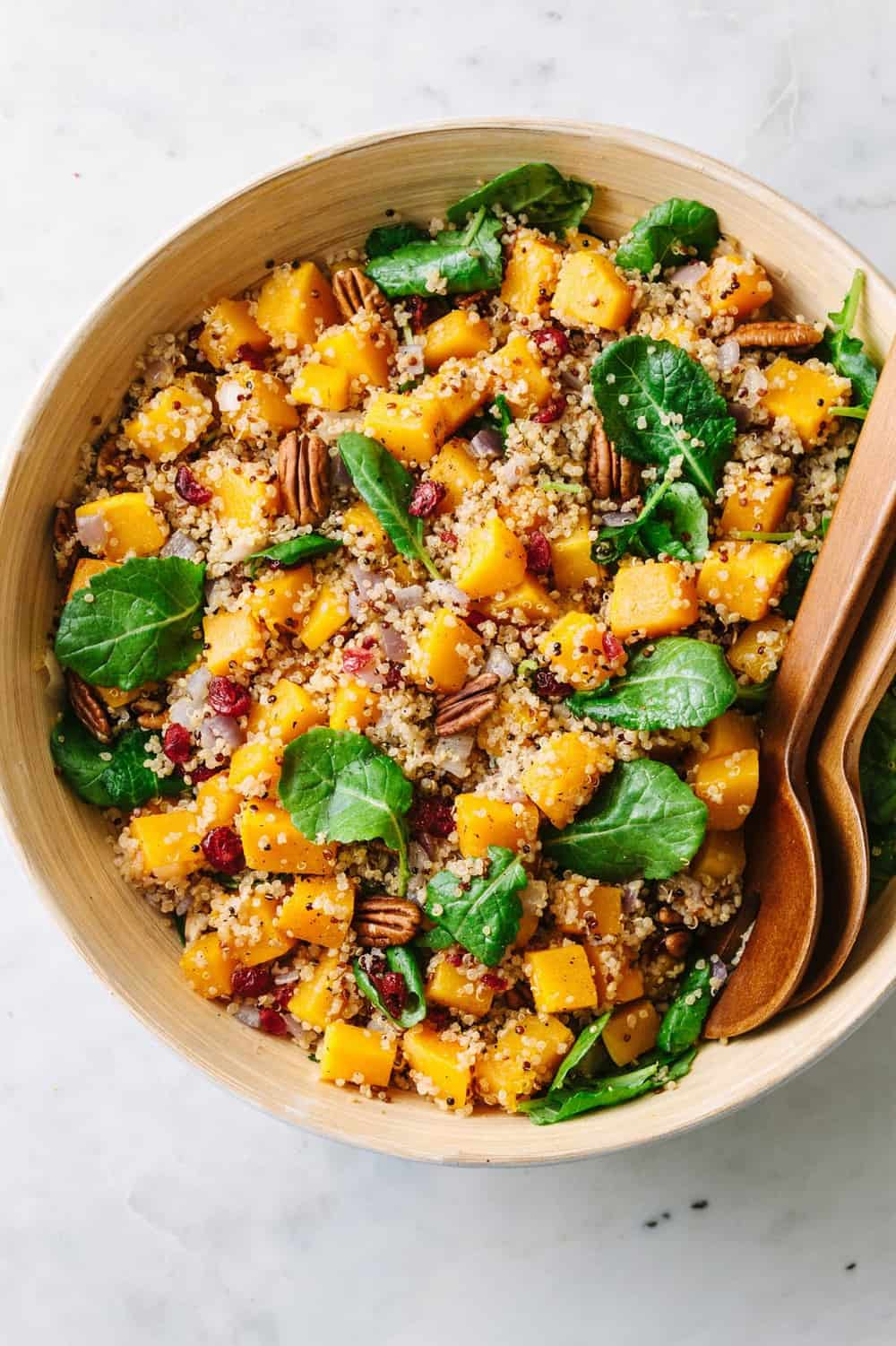 butternut squash quinoa salad mixed together in a mixing bowl with wooden utensils