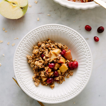 healthy apple cranberry crisp in a white bowl with fork