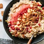 cinnamon oatmeal in a black bowl topped with cranberry applesauce, diced apples, pecans, pumpkin seeds, pomegranates, cinnamon and pure maple syrup