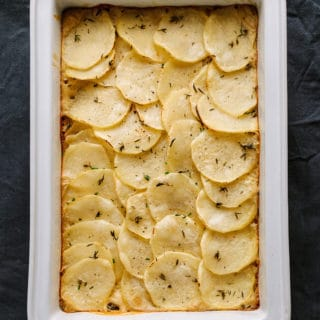 creamy vegan scalloped potatoes in a white baking dish