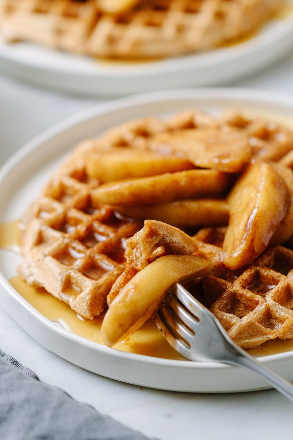 side view of best applesauce waffles sliced and on a fork ready to eat