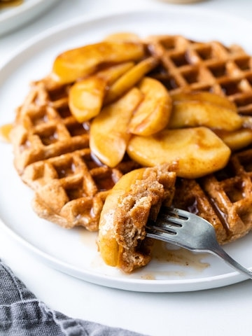 side angle view of cinnamon applesauce waffles with fork.