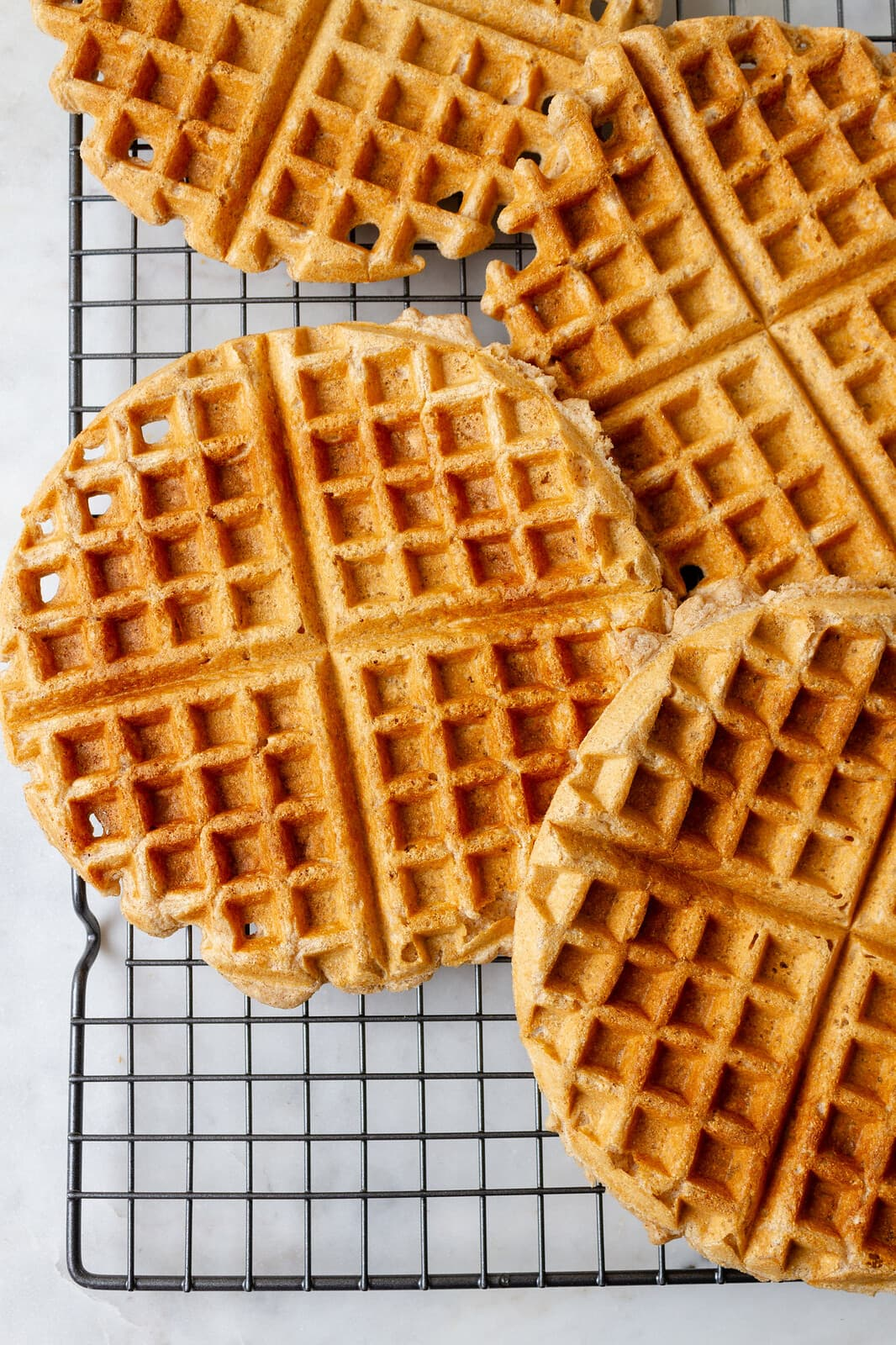 top down view of freshly made applesauce waffles cooling on a wire rack.
