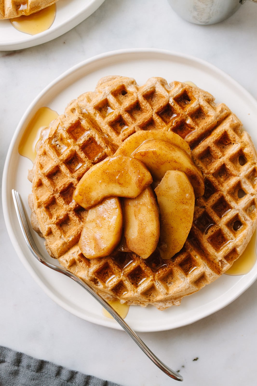 top down view of plate with applesauce waffles with skillet cinnamon apples overtop.