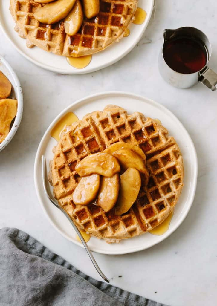 healthy, vegan applesauce waffles on a white plate with warm skillet cinnamon apples