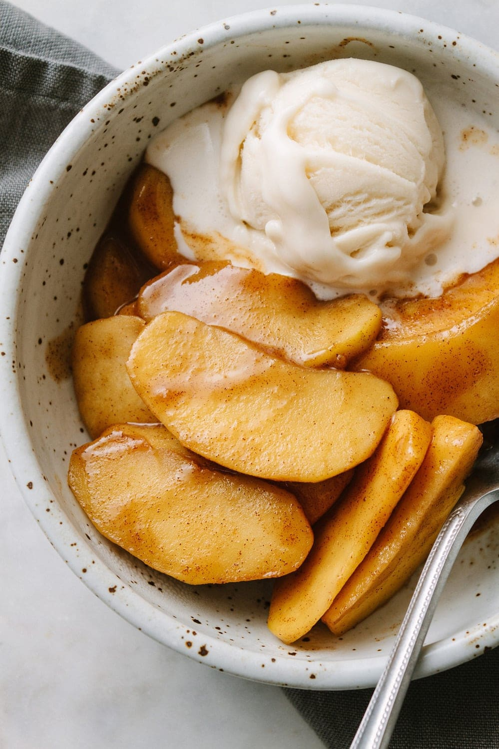 warm spiced cinnamon apples in a bowl with non-dairy vanilla ice cream