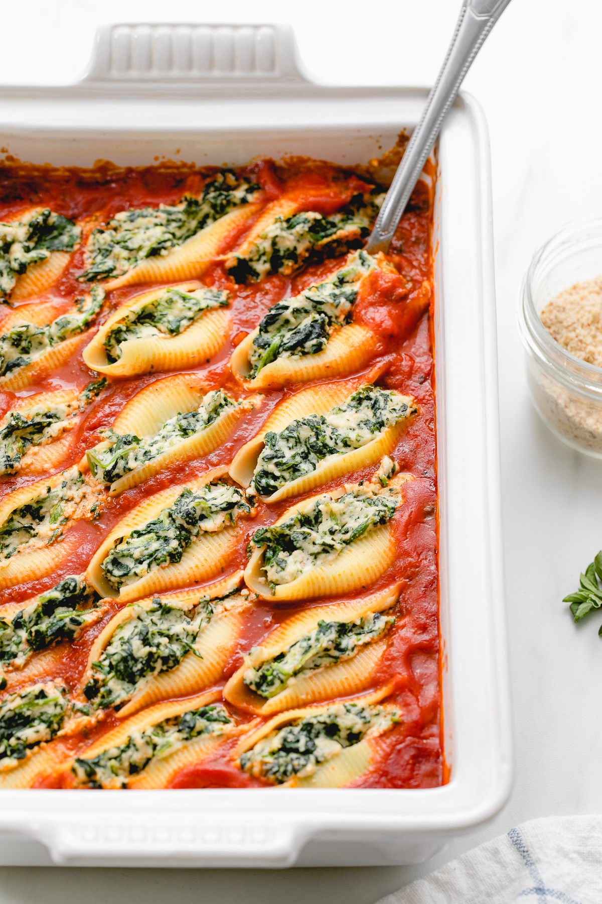 side angle view of vegan stuffed shells in a baking dish with items surrounding.