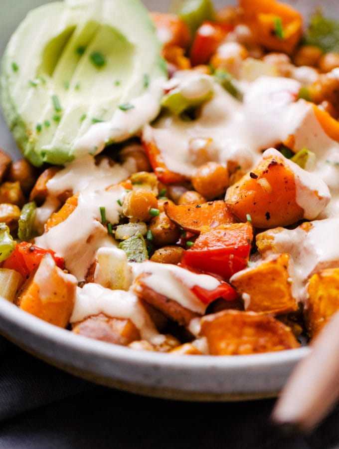chickpea sweet potato breakfast hash with avocado, chives and creamy spicy tahini dressing in a bowl