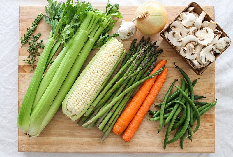 vegan recipes by ingredient: celery, corn, asparagus, carrots, mushrooms, onion and green beans on a wooden cutting board