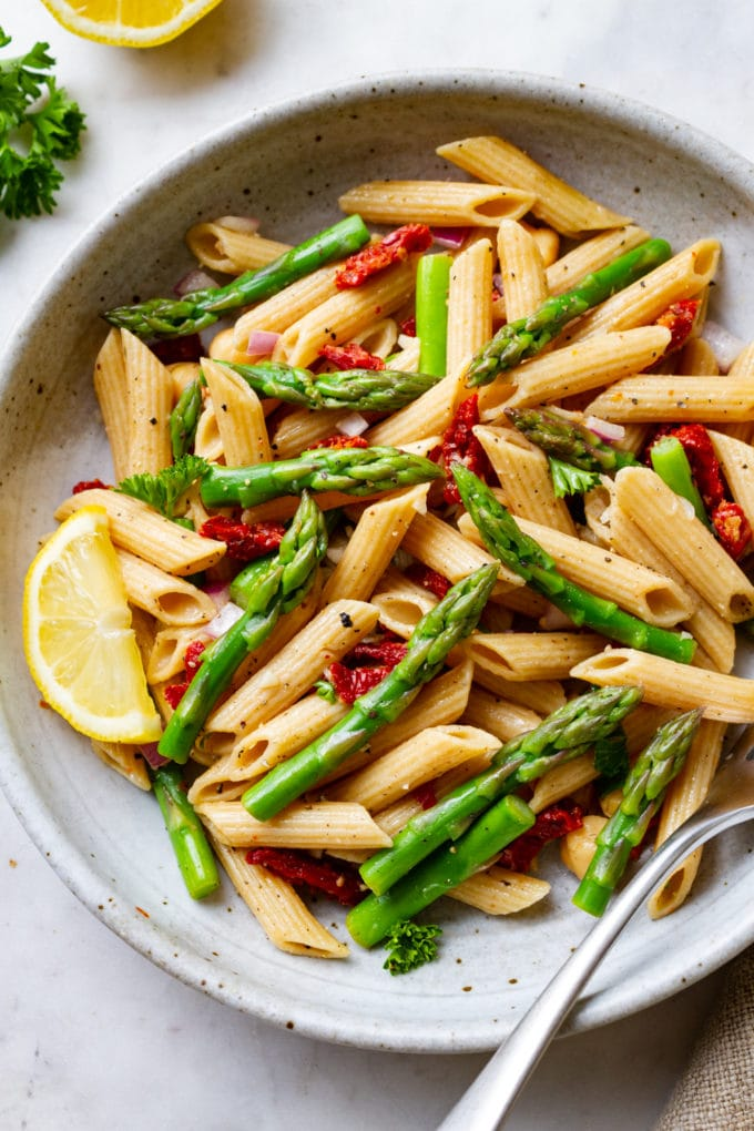 top down view of lemony asparagus pasta salad in a handmade ceramic bowl with fork
