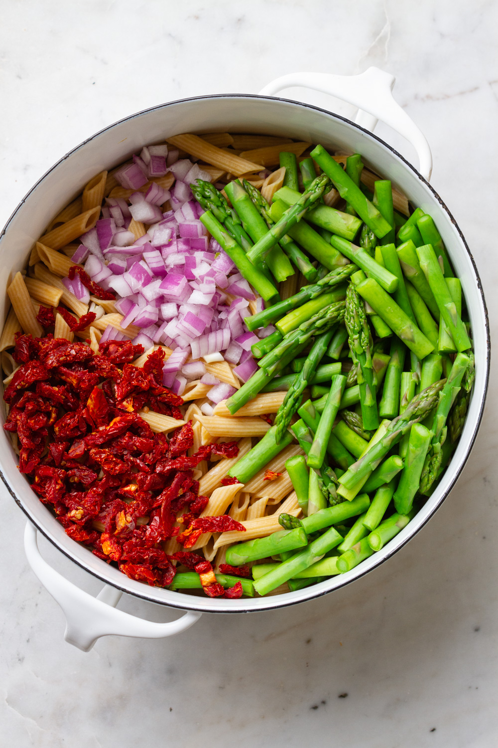 top down view of freshly cooked whole grain pasta with asparagus, sun-dried tomatoes, red onion, before adding the dressing and being mixed in a white pot
