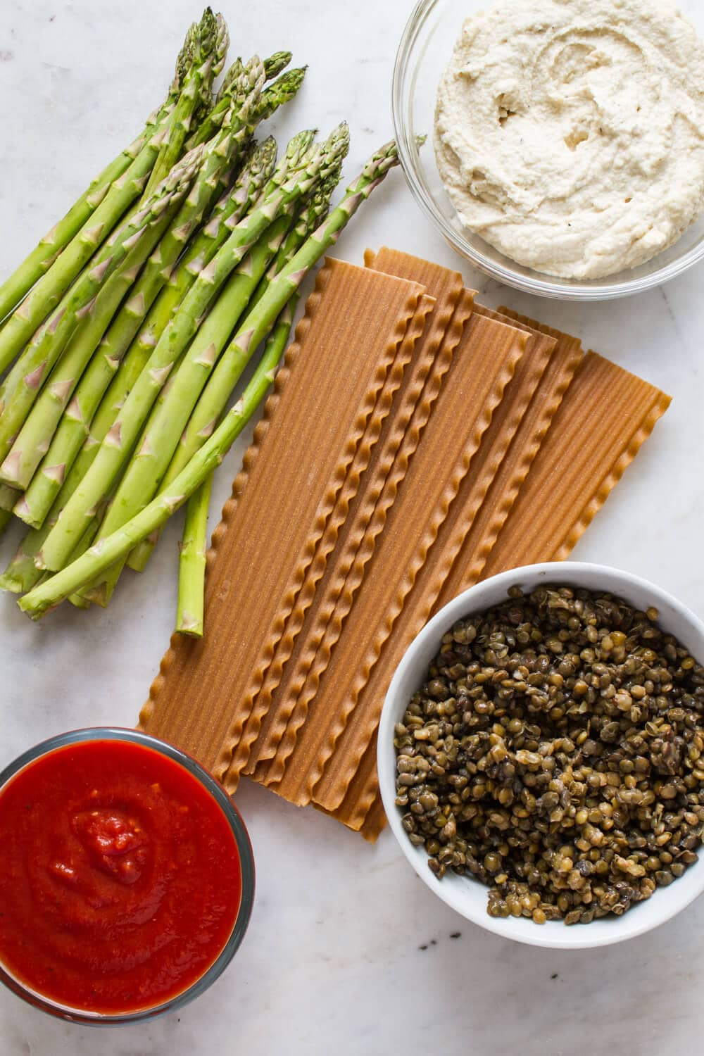 ingredients for vegan lasagna laid on a marble slab, including noodles, pasta sauce, cashew ricotta cheese, lentils and fresh asparagus